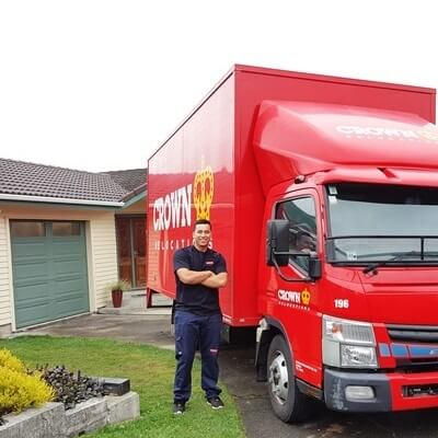 Domestic packer and mover in front of Crown Relocations movers truck